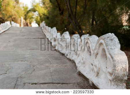 A long path of a path from a large stone tile leads to the sea of the ocean, among the green of bushes and trees, past a fence of white curly tiles, the beach beach seaside vacation summer sun