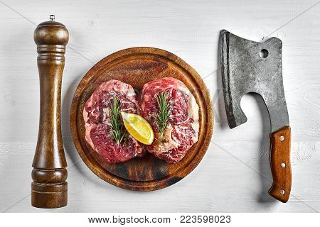 Two raw beef steak with spices on wooden board and kitchen ax on white background, top view. Copy space. Still life. Flat lay