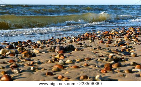 sea stones in the sand, the sea coast with stones and sand