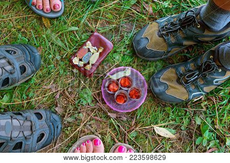 four glasses, four pairs of legs, four candies, a picnic