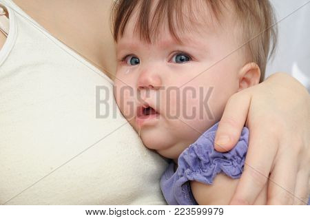 Crying baby at the mother on hands. Soothing upset child embracing and calming. Mother and daughter
