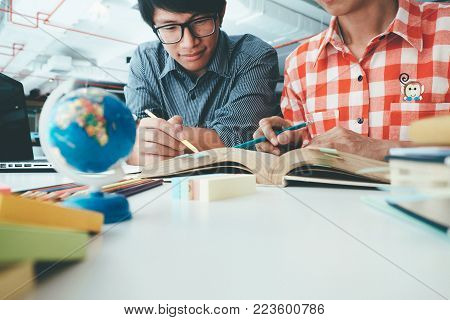 Young woman and man studying for a test an exam. Tutor books with friends. Young students campus helps friend catching up and learning. People, learning, education and school concept.