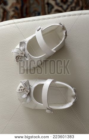 The white shoes for child's christening on white background