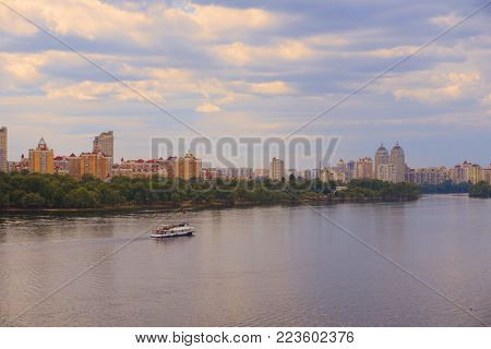 Yacht (ship, boat) goes on surface of Dnieper (Dnipro, Dnepr) river against background of city skyscrapers with yellow blue sky