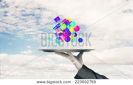 Cropped image of waiter's hand in white glove presenting multiple cubes on metal tray with cloudy skyscape on background. 3D rendering.
