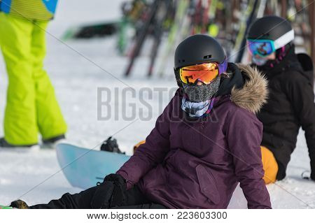 A Snowbord sitting on the snow in a purple jacket and reflective glasses. Mountain holiday concept, sport. Sunny day in Dolomites. Val di Fiemme. Italy