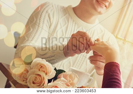 Man Putting On Girlfriend Finger Engagement Ring
