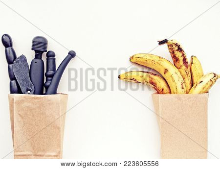 A paper bag with ripe yellow bananas and a paper bag with black sex toys on a light background. The idea for sex shop advertising. Shopping for adults