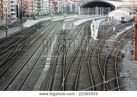 Railroad tracks and catenary with crossings of roads and sidewalks. Bilbao Spain. poster