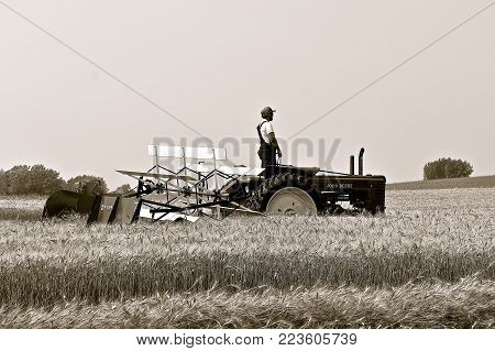 ROLLAG, MINNESOTA, Sept 2, 2017: An unidentified operator of a B John Deere tractor  is demonstrating with a McCormick swather at the annual WCSTR farm show in Rollag held each Labor Day weekend where 1000's attend. (black and white)