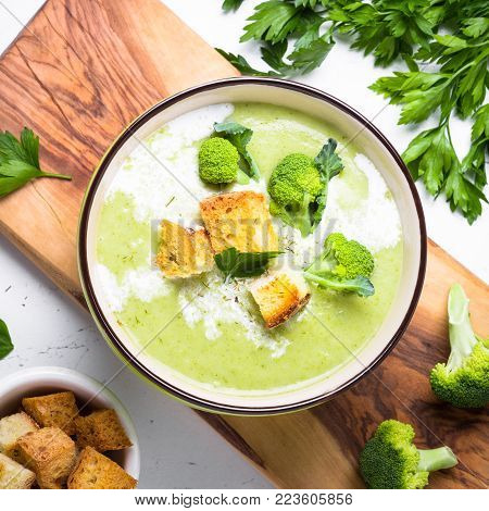 Green soup puree or cream soup with broccoli and greens on white table. Top view. Square.