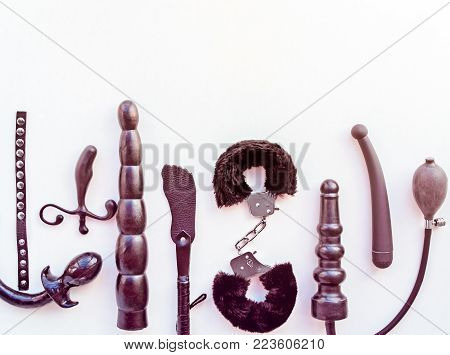 Different sex toys: dildo, prostate massager, vibrator, anal plug, handcuffs and others. Objects are located on a light background
