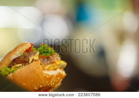 A fast food cheeseburger with a bite taken out of it one bite taken out of it Bitten hamburger.