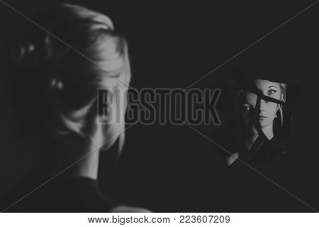 Woman looking at her face in shards of broken mirror pieces artistic conversion