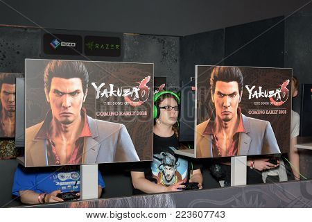 Cologne, Germany - August 24, 2017: Young woman plays concentrated the game Yakuza at Gamescom 2017. Gamescom is a trade fair for video games held annually in Cologne.