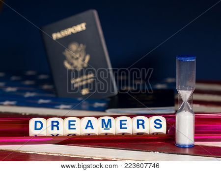 Dreamers children spelling letters on wooden USA flag with passports for citizenship and hourglass