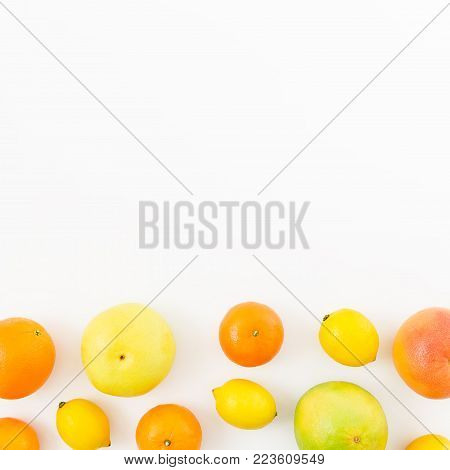 Fruits frame made of lemon, orange, grapefruit, sweetie and pomelo on white background. Flat lay, top view.