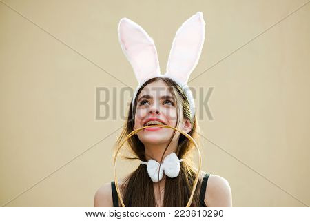 Woman smiling with bunny ears and bow. Girl holding wicker handle in teeth. Happy Easter model with long, brunette hair on beige background. Tradition and symbol. Easter holiday celebration concept