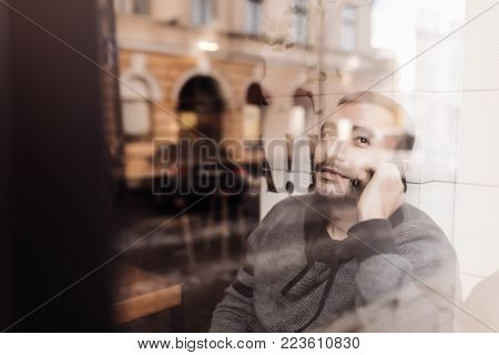 Enjoying His Phone Call. Handsome Man Talking On Mobile Phone And Looking Throughwindow With Smile W