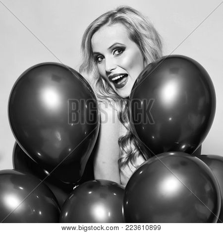 One beautiful smiling flirtatious young happy blond woman with long curly hair standing in bunch of red party balloons in studio on yellow backdrop, square picture