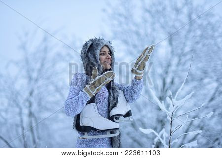 Girl skater with figure skates in fur hat, mittens, sweater smile in snowy forest outdoor. Winter fashion, style. Vacation, holidays, hobby, lifestyle. Ice skating, sport, activity, health concept.