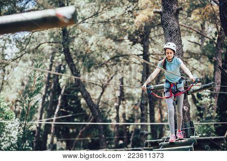 Happy school girl enjoying activity in a climbing adventure park on a sunny day