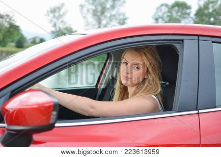 Young, attractive blonde girl in new red car who frowns, with a facial expression Really? Don't tell me...