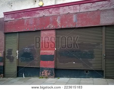 derelict abandoned store with shuttered vandalized shop front with peeling red paint on an urban street