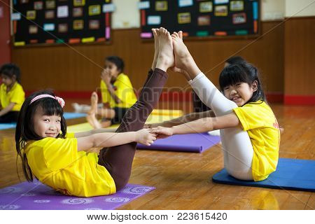 Young Children Take A Yoga Class With Their Teacher.
