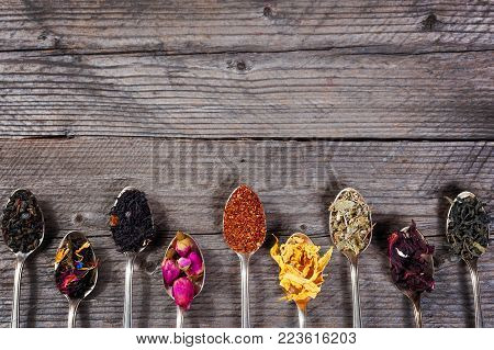 Various kinds of tea in spoons on wooden background. Dry Tea assortment. Top view, copyspace.