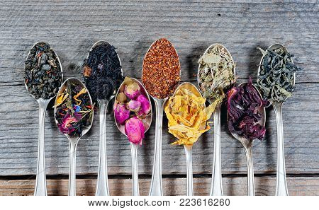 Various kinds of tea in spoons on wooden background. Dry Tea assortment. Top view.