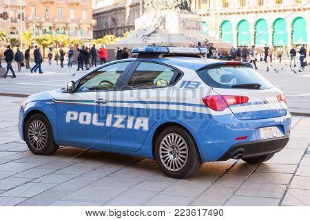 Milano, Italy - January 19, 2018: Blue and white Alfa Romeo Giulietta, Italian police car patrols Piazza del Duomo, central city square of Milano, rear view