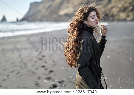 Pretty Smiling Girl With Closed Eyes Is Posing On The Black Sand Beach On The Background Of The Rock