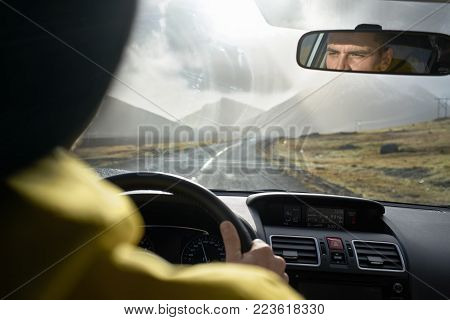 Guy Is Driving A Car On The Country Roadway Between Brown Fields On The Background Of The Mountains