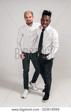 International friendship concept. Studio shot of two stylish young men: handsome bearded young man in white shirt and jeans standing next to his African-American friend on white background