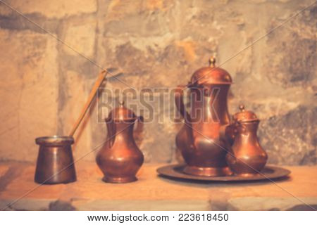 Antique brass retro teapot and coffee set. Vintage filter effect. Copy space. Blur rustic background.