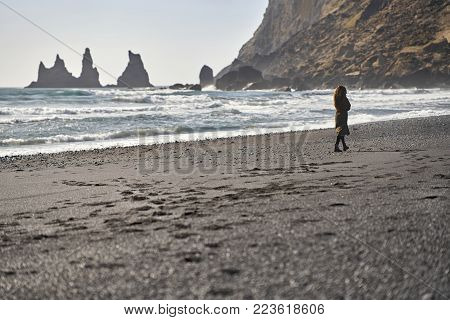 Curly Girl Walks On The Black Sand Beach On The Background Of The Rocky Cliffs And The Stormy Sea In