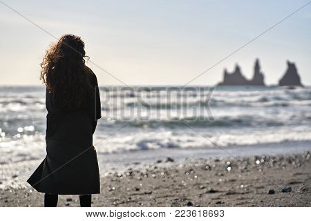 Woman Stands On The Black Sand Beach On The Background Of The Stormy Sea And Rocks In Iceland.she We