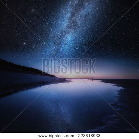 Sea shore in night with stars reflected in water. Fine art landscape