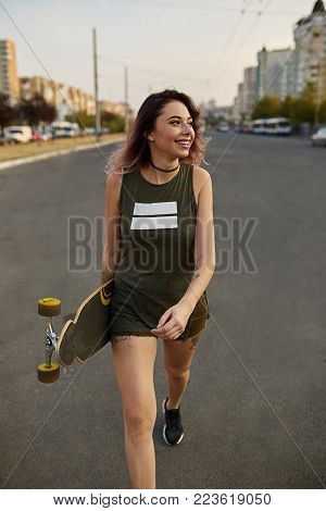 Careless beautiful girl with tattoos posing with a colorful longboard while walking on the road in the city