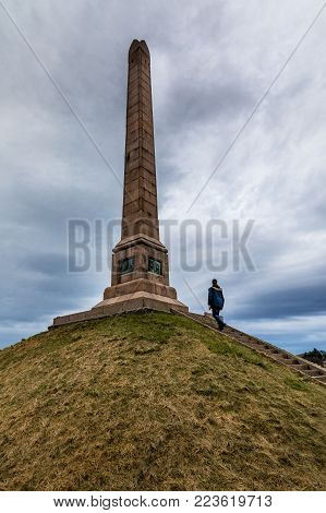 Haraldshaugen, an old tumulus, with the National Monument, in Haugesund, Norway. Tradition holds that the old Norse Harald Fairhair was buried here around year 933. The monument was unveiled on July 18, 1872. Man walking the stairs up to the monument.