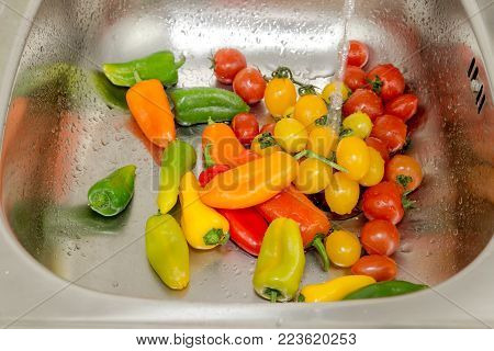 Washing of peppers and cherry tomatoes in a metal sink under a stream of water close-up