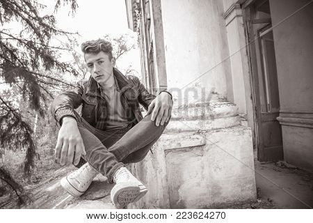 portrait of a guy in a leather jacket among the shabby walls