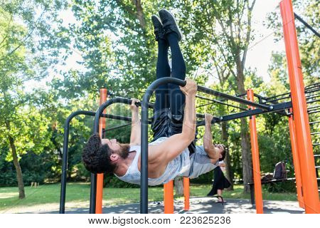 Two muscular young men practicing together calisthenics workout for strength and balance in an outdoor fitness park with modern equipment