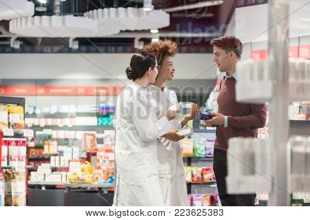 Young man asking for advice and opinion from two experienced female pharmacists regarding a prescribed pharmaceutical product in the interior of a modern drugstore