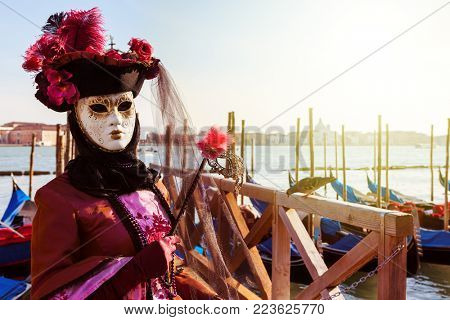 VENICE, ITALY - MARCH 04, 2011: Unidentified participant wears costume and mask in front of Grand canal during famous annual Carnival taking place each year in Venice.