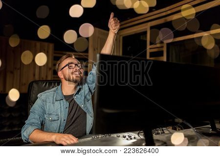music, technology, gesture and people concept - happy man at mixing console in sound recording studio showing thumbs up over lights