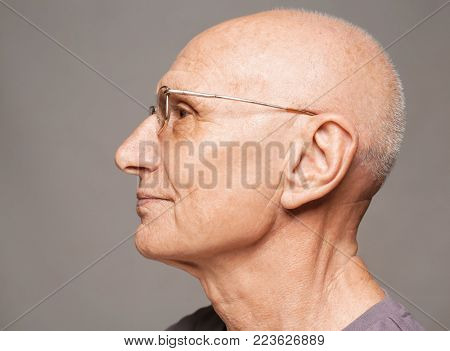 Elderly man on grey background. Hearing problem
