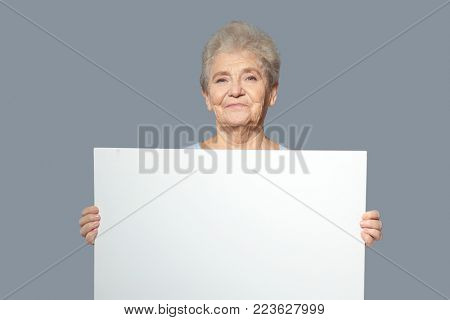 Senior woman with blank advertising board on grey background