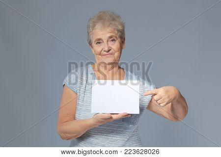 Senior woman with blank sheet of paper for advertising on grey background